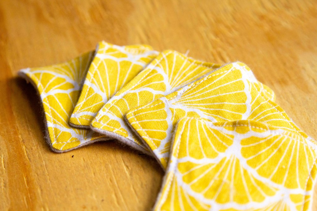 A set of 5 yellow printed facial wipe squares fanned out on top of a light wooden surface.