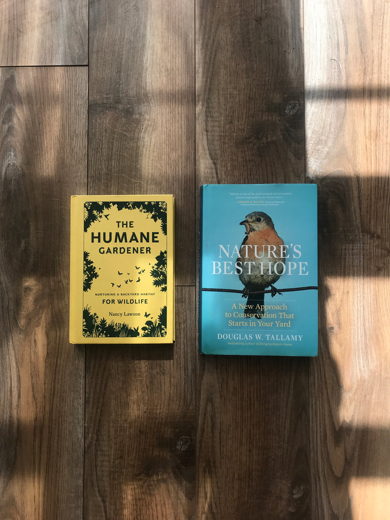 A yellow book (The Humane Gardener) and blue book with a bird (Nature's Best Hope) lie on a wooden floor. A window is casting light and shadow all across the books and floor.