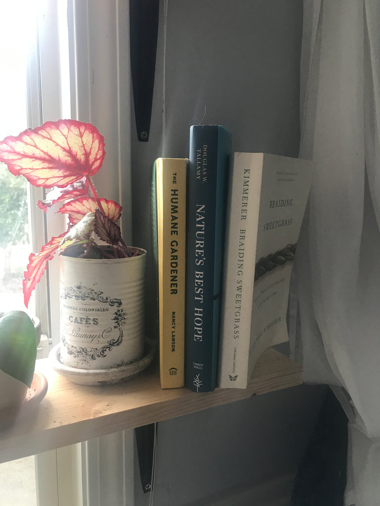 Three books (The Humane Gardener, Nature's Best Hope, and Braiding Sweetgrass) sit on a light wooden shelf next to a reddish plant in a white tin can