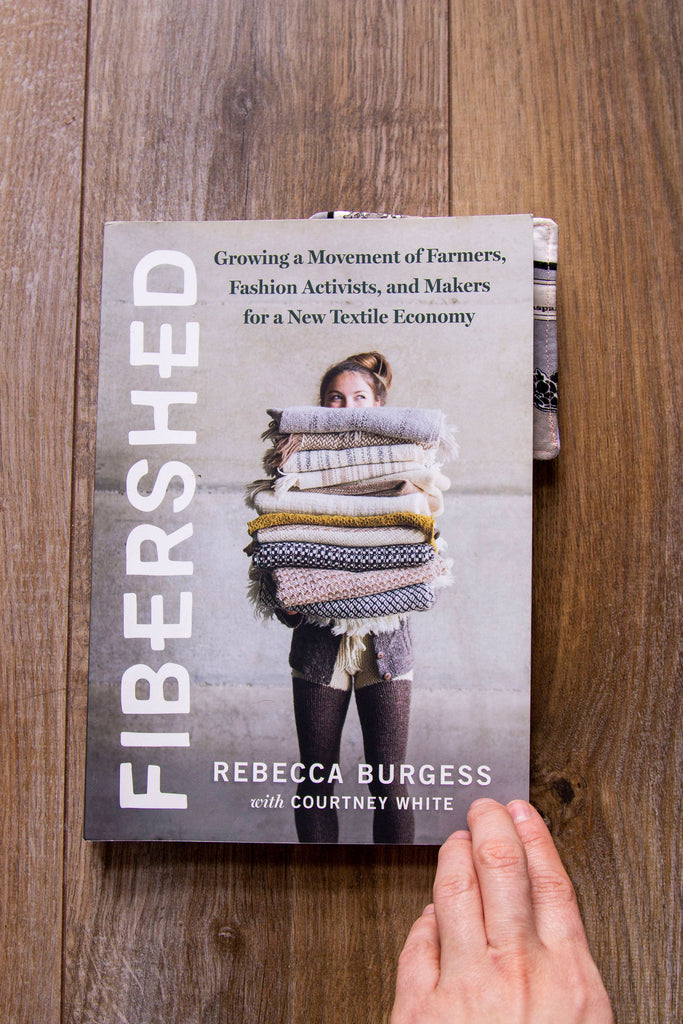 """A straight on image of a book laying against a dark wood floor. The title of the book is along the left side and reads """"Fibershed"""" in white letters against a grey background. On the center of the cover is a white woman holding a variety of hand knit and woven fabrics with her head peeking up. Above her head reads """" Growing a movement of farmers, fashion activists, and makers for a new textile economy."""" At the bottom of the cover it reads """"Rebecca Burgess with Courtney White"""" in white lettering"""