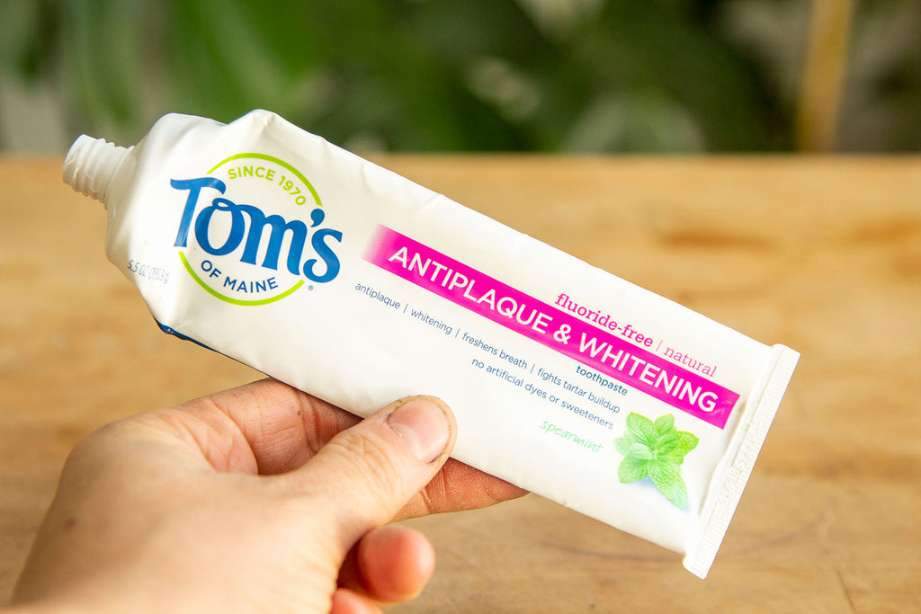 A white Toms toothpaste bottle being held up by white hands with a light wood table in the background