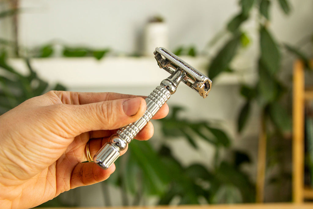 A white hand holds an all metal safety razor in front of a background of out of focus plants.