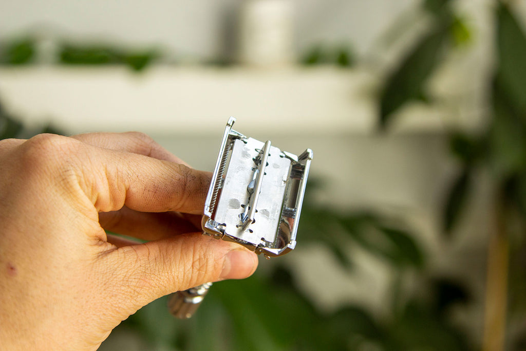 A white hand holds an all metal safety razor in front of a background of out of focus plants showing how the mechanism opens at the top like a pair of french doors