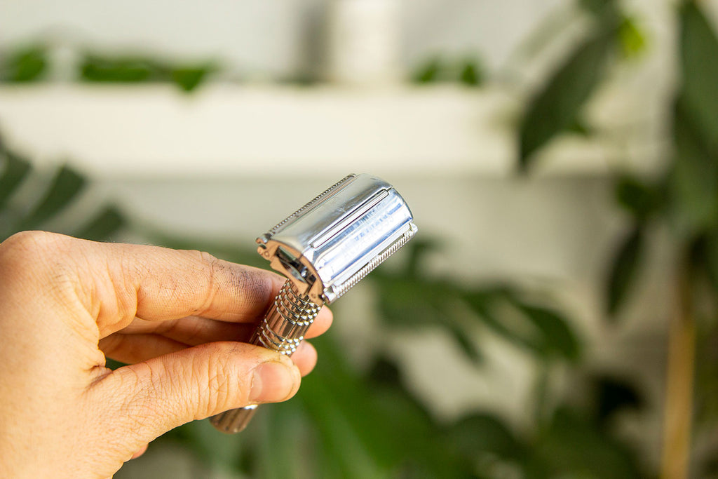 A white hand holds an all metal safety razor in front of a background of out of focus plants showing how the top closes to secure the blade safely