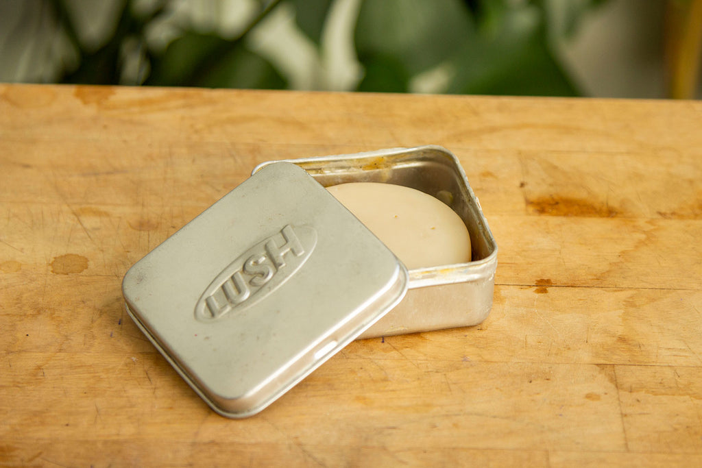 """A light beige circular bar of soap sits inside a square metal tin on top of a light wood table with greenry in the back. A metal lid is slightly ajar, showing the soap inside the tin. The front of the lid reads """"Lush"""""""