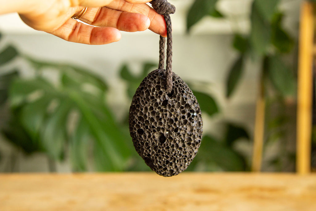 A white hand dangles a black pumice stone AKA lava rock above a wooden table with greenery just out of focus in the background