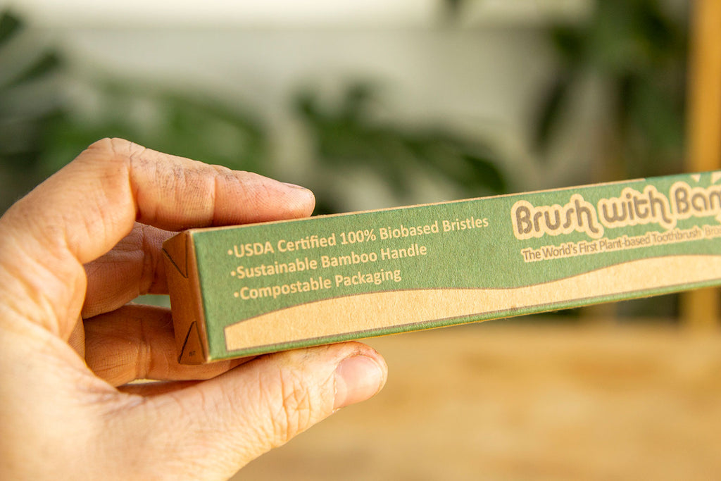 A white hand holds a tooth brush cardboard packaging showing that the bristles are biobased, the handle is fully compostable, and the cardboard box is biodegradable.