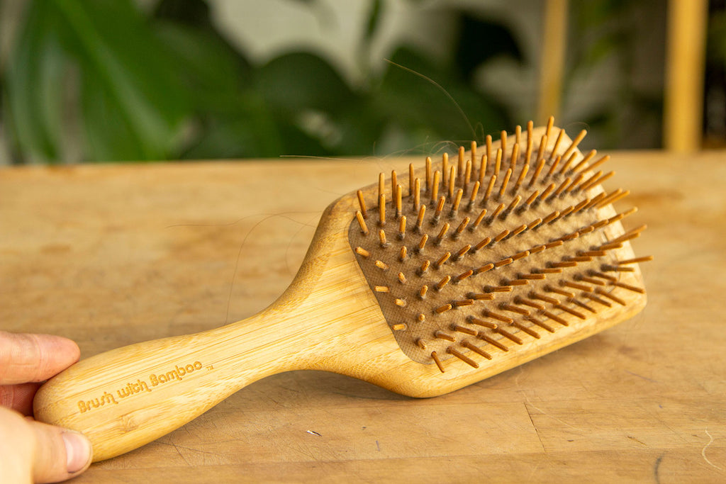 A bamboo hair brush with bamboo bristles sits on a light wooden countertop with greenery in the background and out of focus.