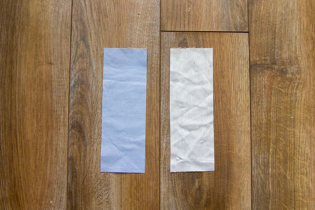 A blue fabric rectangle sits to the left of a muslin fabric rectangle on top of a dark wooden floor