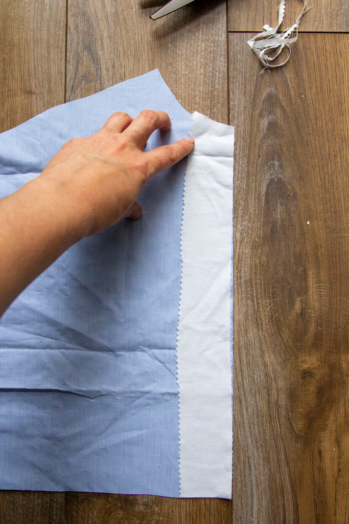 A pair of white hands has placed the rectangular muslin piece on top of the blue fabric along a straight edge on the right hand side. The finished edge of the interfacing is facing towards the inside of the blue fabric.