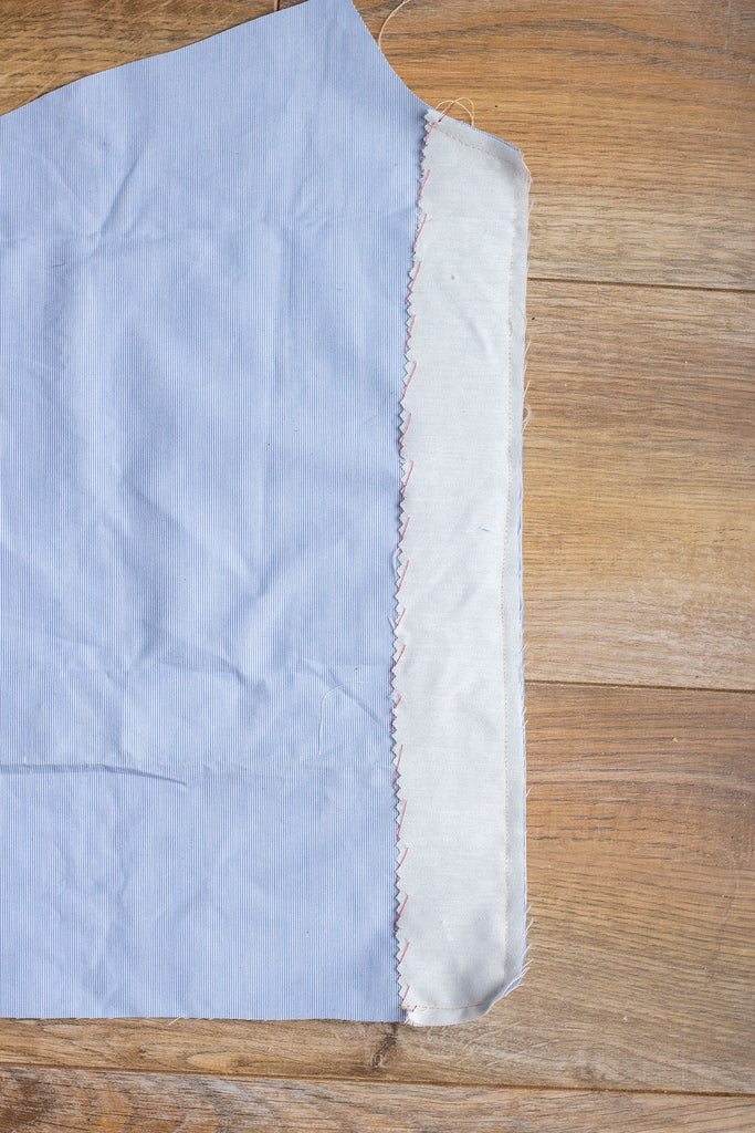 A straight on shot of the wrong side of the blue garment with muslin interfacing along the right side of the fabric. There are a line of red stitches seen against the muslin interfacing. Part of the blue garment is cropped from view.