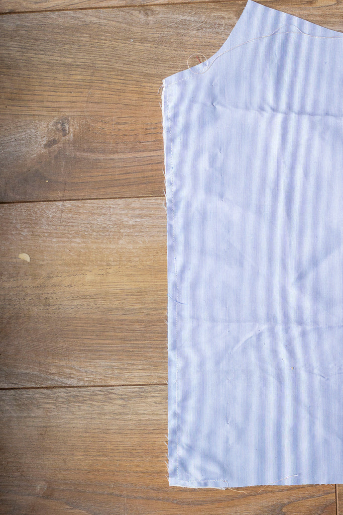 The right side of the blue garment where none of the red stitches can be seen. Part of the blue garment has been cropped from the right side of the frame