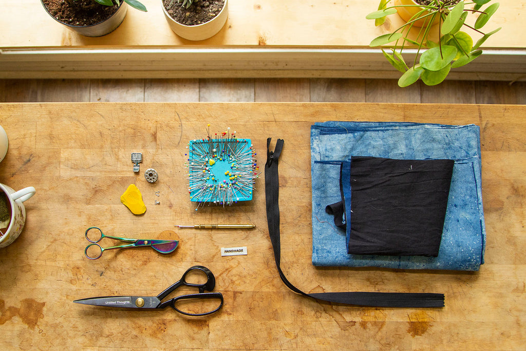A flat lay of the supplies needed for this sewing project including scissors, hook and eye, zipper, pins, etc.