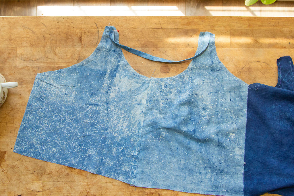 A dual toned blue bodice is laid out on a wooden cutting table with a strap basted to it's strap openings.