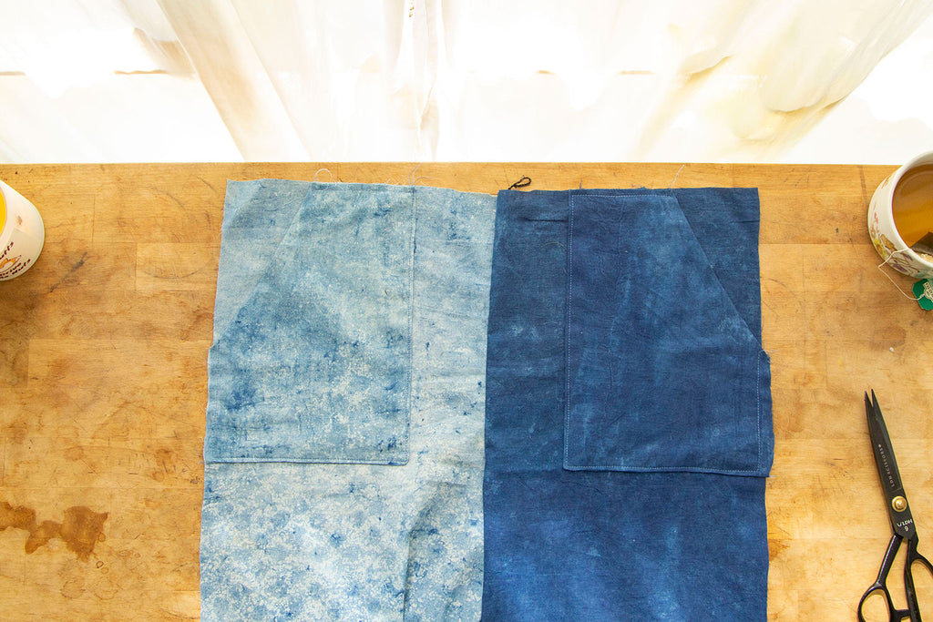 A dual toned blue pair of pants with patch pockets is laid out on a natural cutting board with light streaming from a window