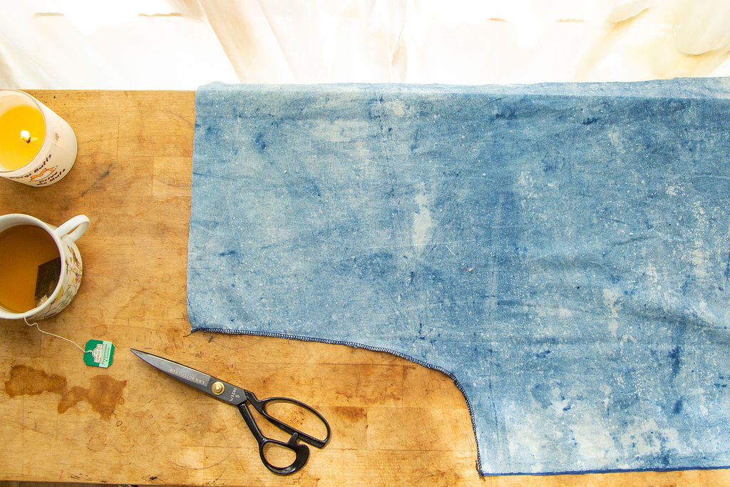 Light blue pant leg with finished crotch seam lying on wooden cutting board
