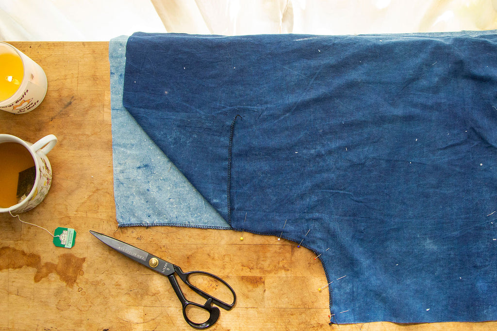 A dark blue pant leg is on top of a light blue pant leg with the crotch seams pinned together stopping at the double notch. a pair of black scissors sits to the side