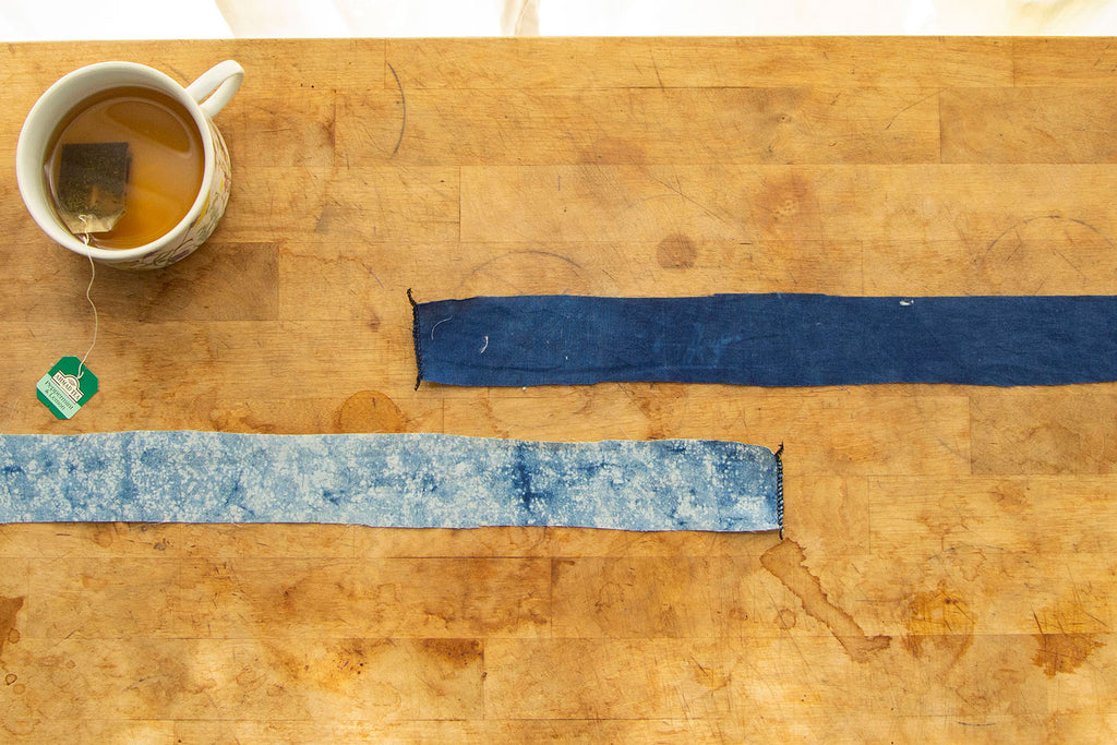 Two different blue colored waist ties are lying on a wooden cutting board, each with a short end serged. A cup of tea sits in the upper left hand corner.