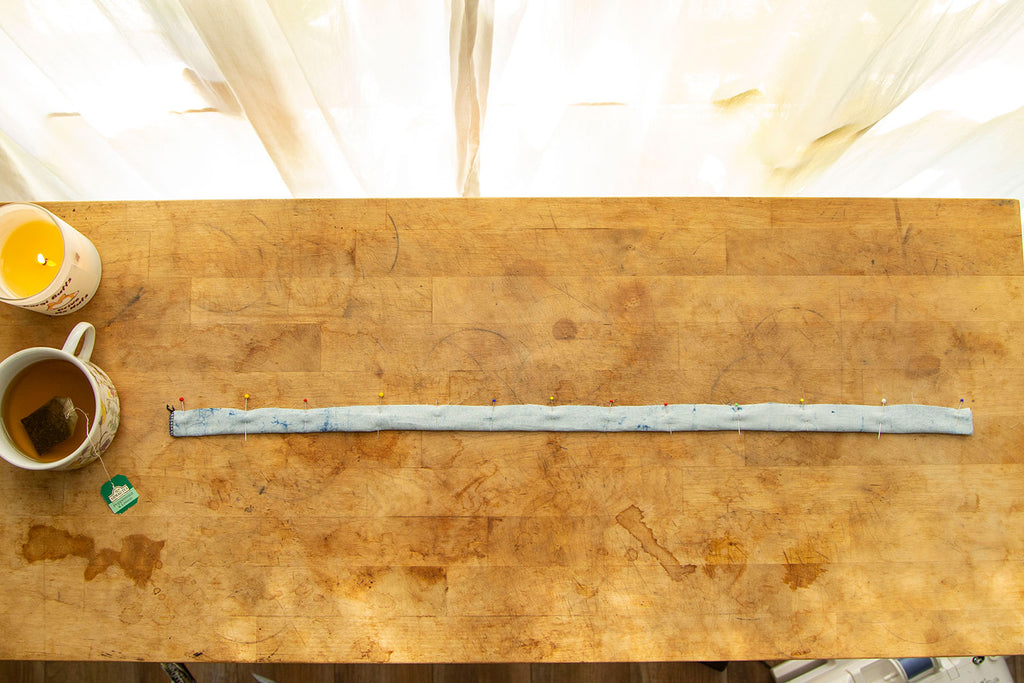 A light blue waist tie folded in half lengthwise and pinned into place. IT sits on a wooden chopping block with a candle and cup of tea in the upper left hand corner.