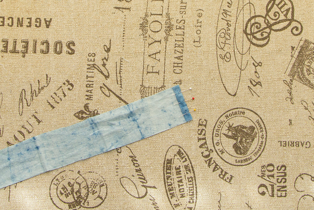A close up of one end of a blue casing with the short end folded back twice and pinned into place. It sits on a light brown ironing board covered in dark brown french writing