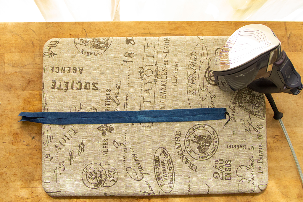 The finished dark blue casing that has just been ironed to look like bias tape sits with an iron in the upper right corner on top of a light brown ironing board with french writing all over it.