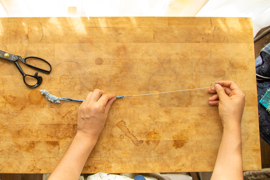 A pair of white hands is pulling the waist tie right side out using a rouleau turner. Underneath this action is a wooden chopping block