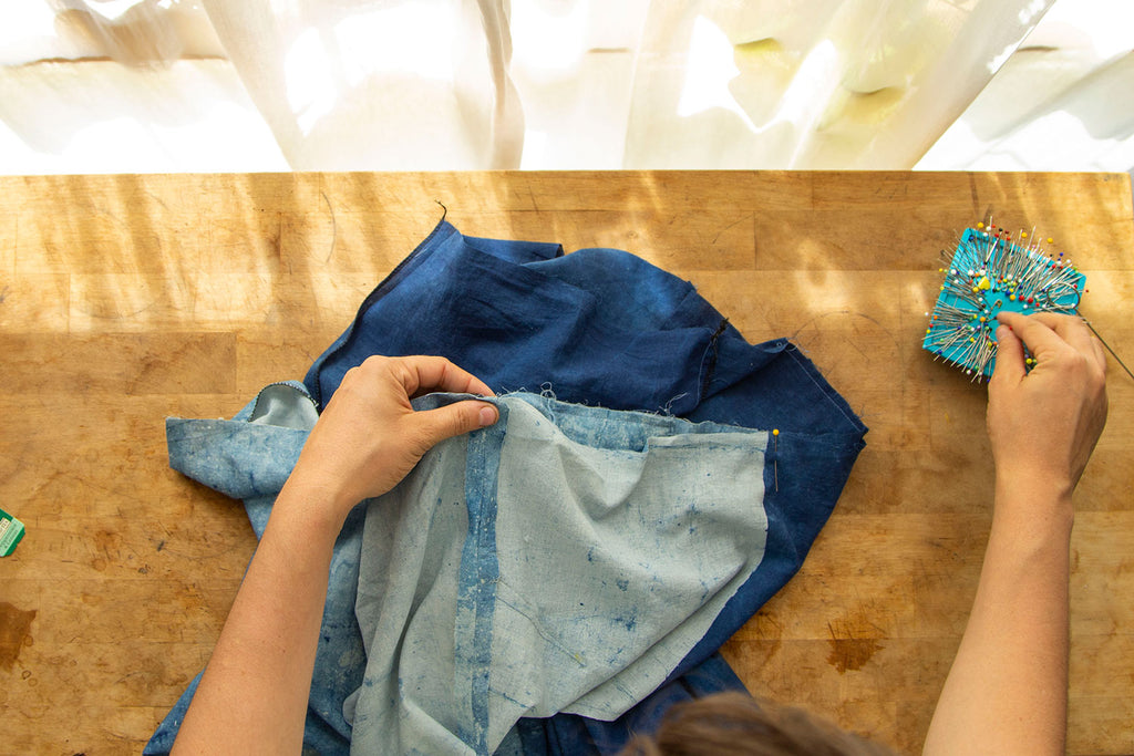 A pair of white hands is attaching the bodice to the pants with right sides together