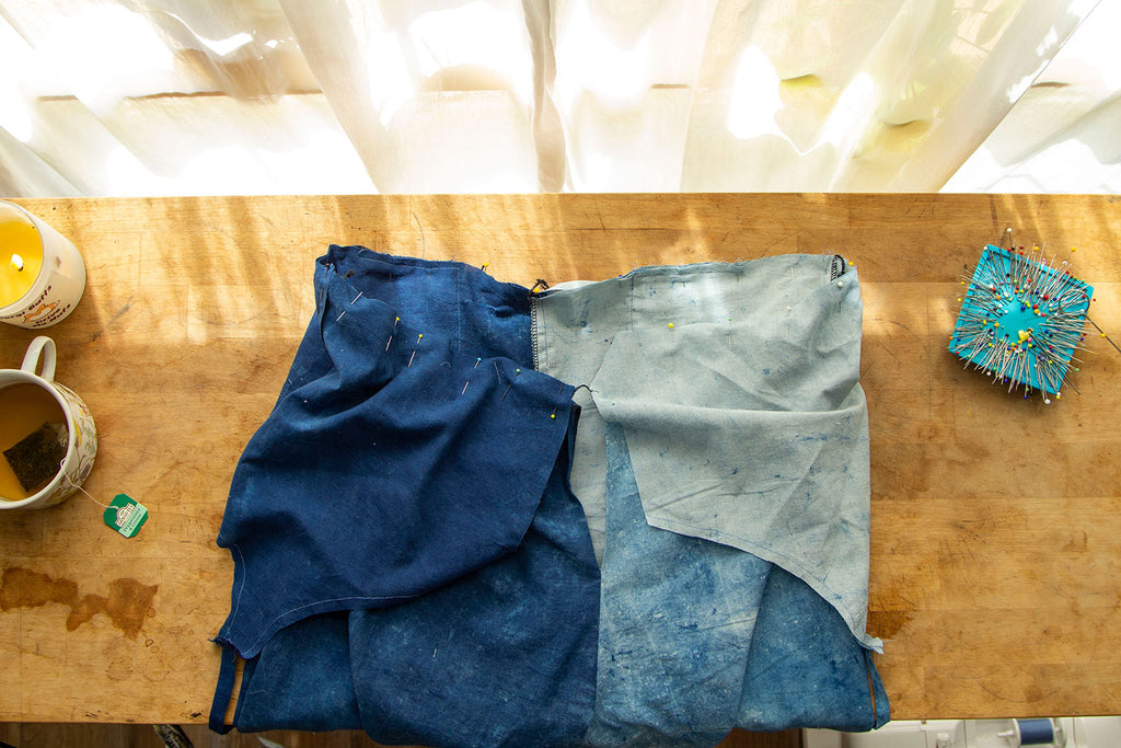 The back opening of the jumpsuit is seen with the bodice and pants having been attached with pins. Dappled light hits the wooden cutting board