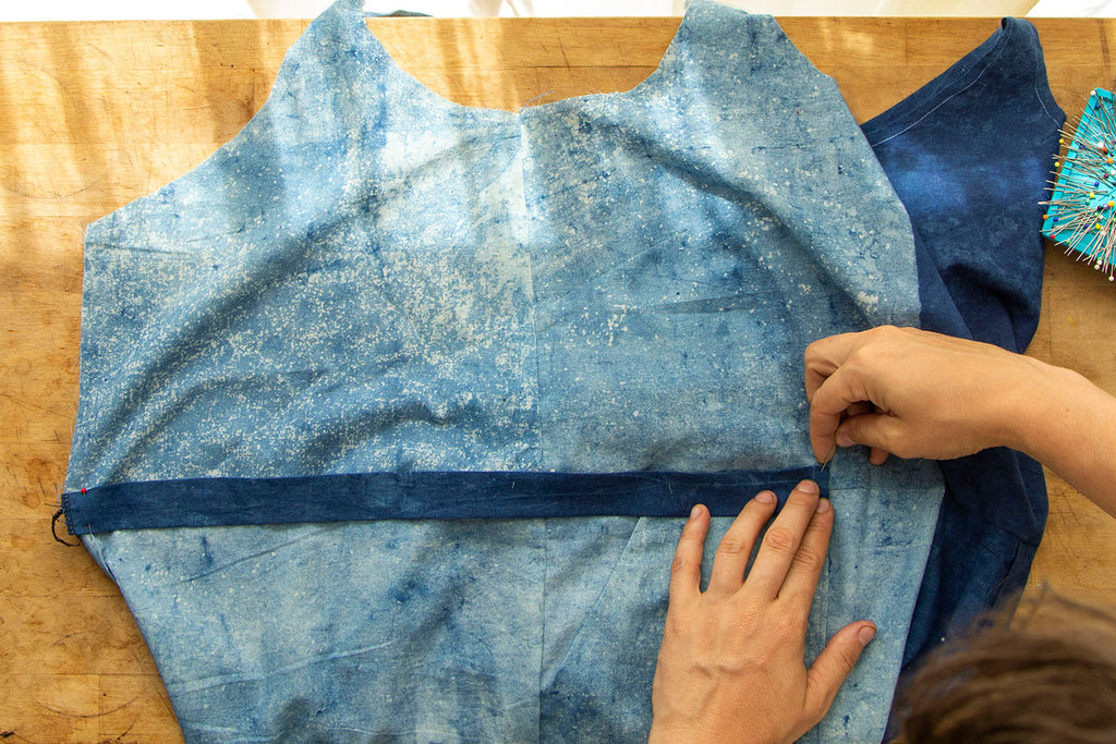 A pair of white hands continues pinning the dark blue casing into place until it reaches the front patch pocket edge