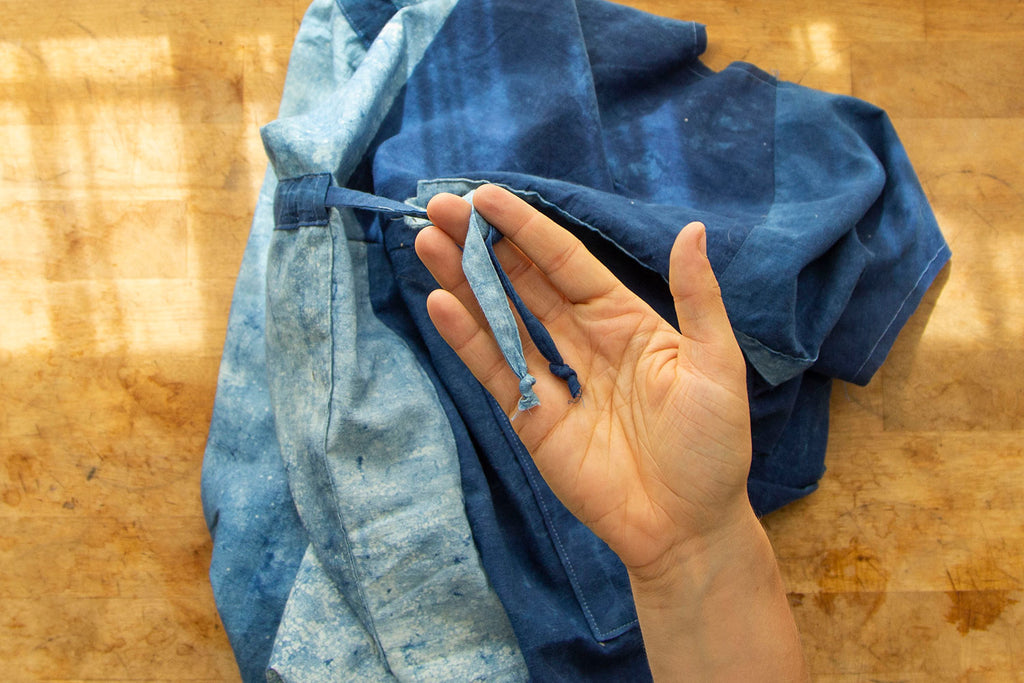 A white hand showcases both ends of the waist ties tied into small knots. The blue jumpsuit is seen in the background.