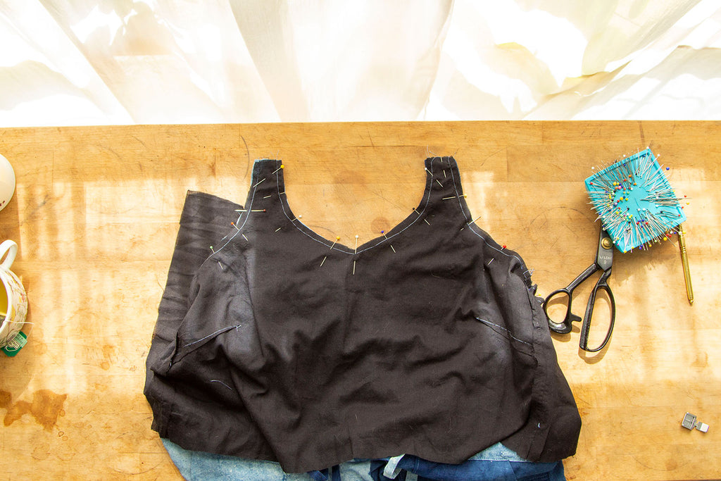 A flat lay of a black bodice lining pinned along the front neckline, strap opening and underarm of the jumpsuit bodice. A pair of scissors and pins is in the right hand corner