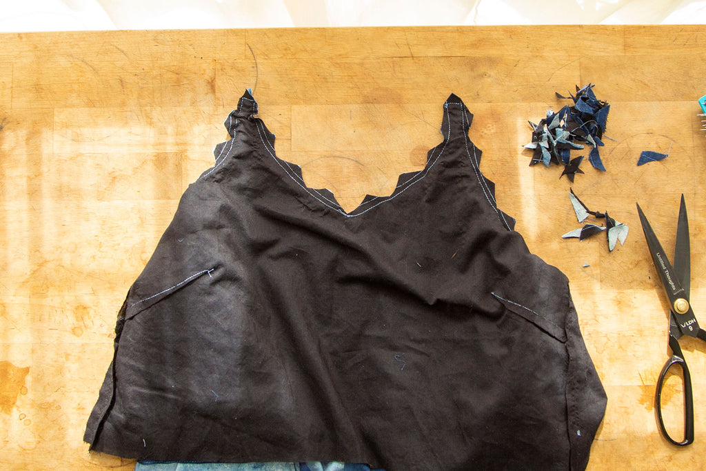 A flat lay of the black lining with loads of little triangles cut out from the front neckline. The scraps of the fabric cut out are sitting in the upper right corner with a pair of black scissors just below them