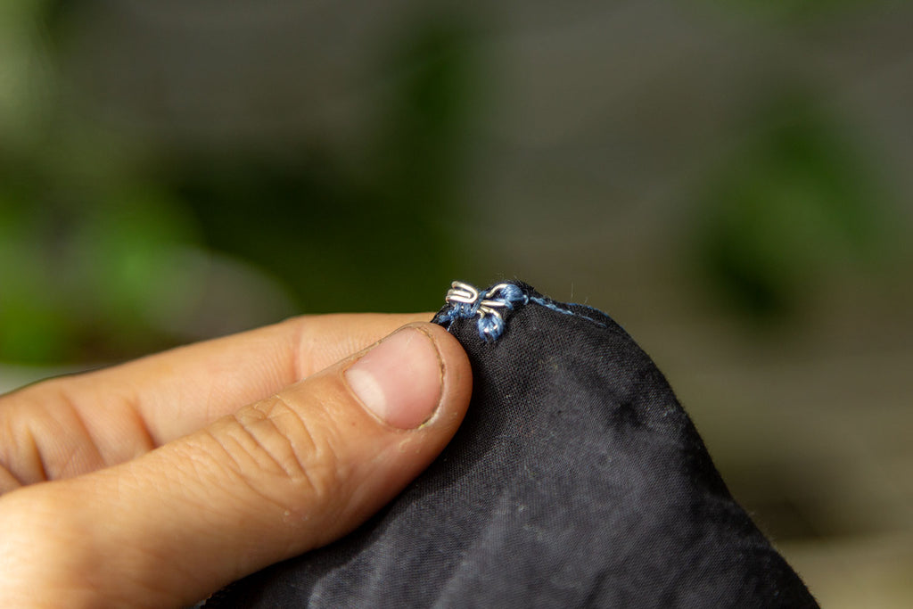 A white hand holds up a small silver hook that has been sewn with blue thread to one side of the inner jumpsuits black lining.
