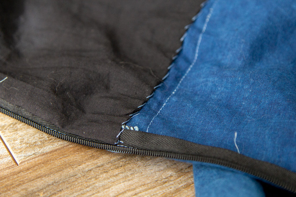 A close up of the hand sewn lining at the CB edge near the invisible zipper. There are visible whip stitches where the lining was delicately attached to the inner jumpsuit