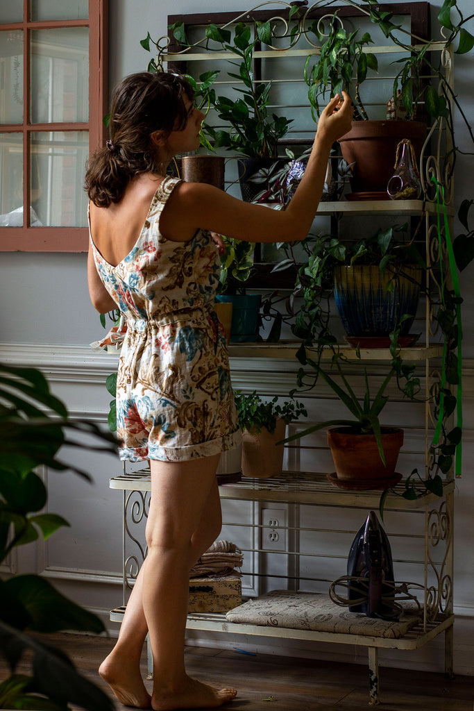 A white woman is standing with her back to the camera and is reaching out to a plant on a white bakers rack filled with many plants. She is wearing a beige colored romper with thick straps and a floral print