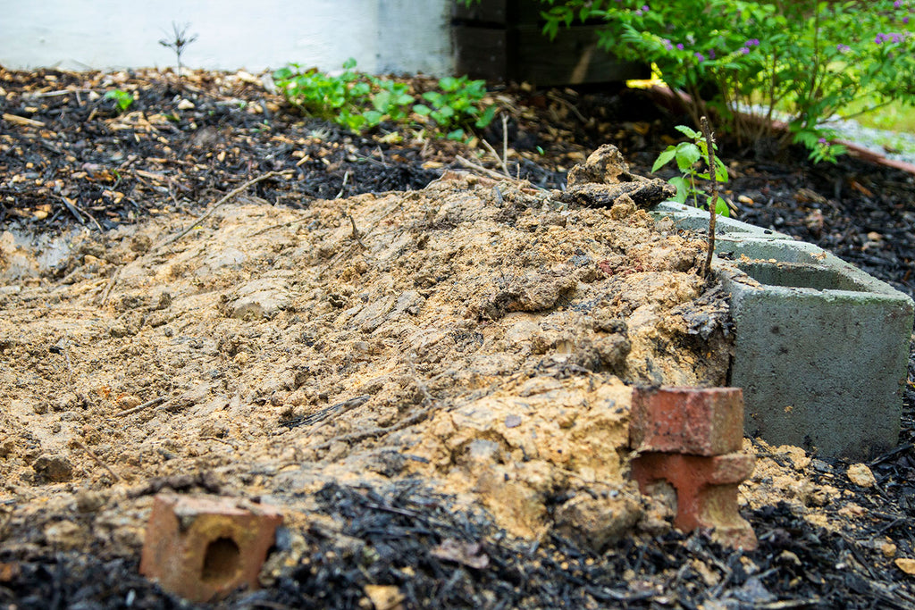 A close up of the gentle dirt slope butting up against the larger cinder blocks
