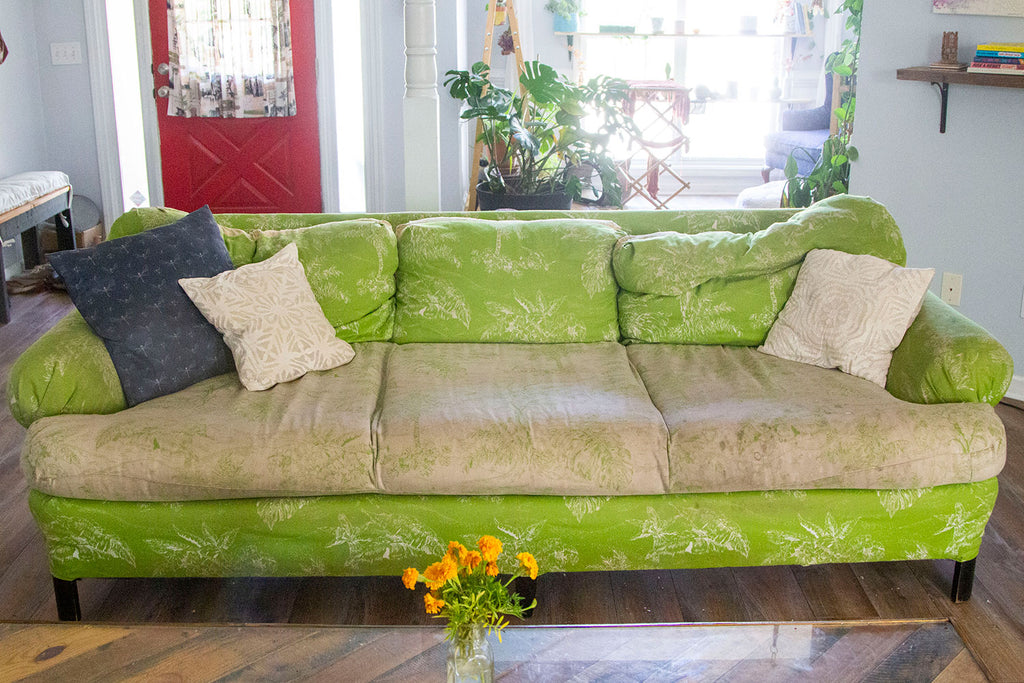Lime green couch with a tropical print and a white set of lower cushions with a lime green print. The lower cushions are a bit dirty from use. A pair of white pillows flanks either side of the couch