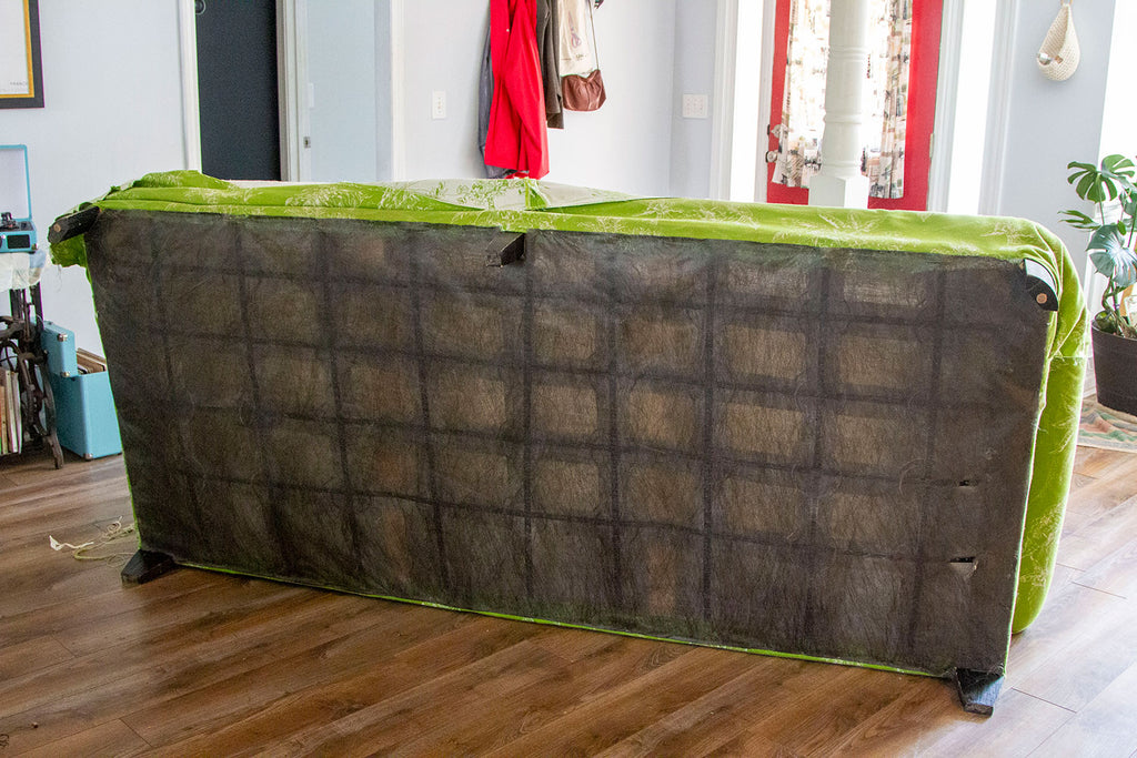 Underside of couch with a black felted fabric hiding the springs