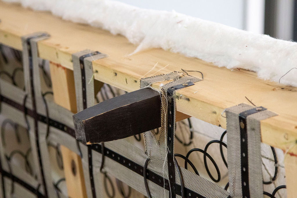 Close up of underside center leg of couch with springs and heavy duty cloth + metal holding springs in place