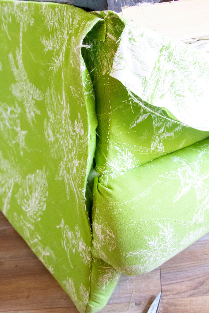 Side image of lime green couch with seams slightly ripped open