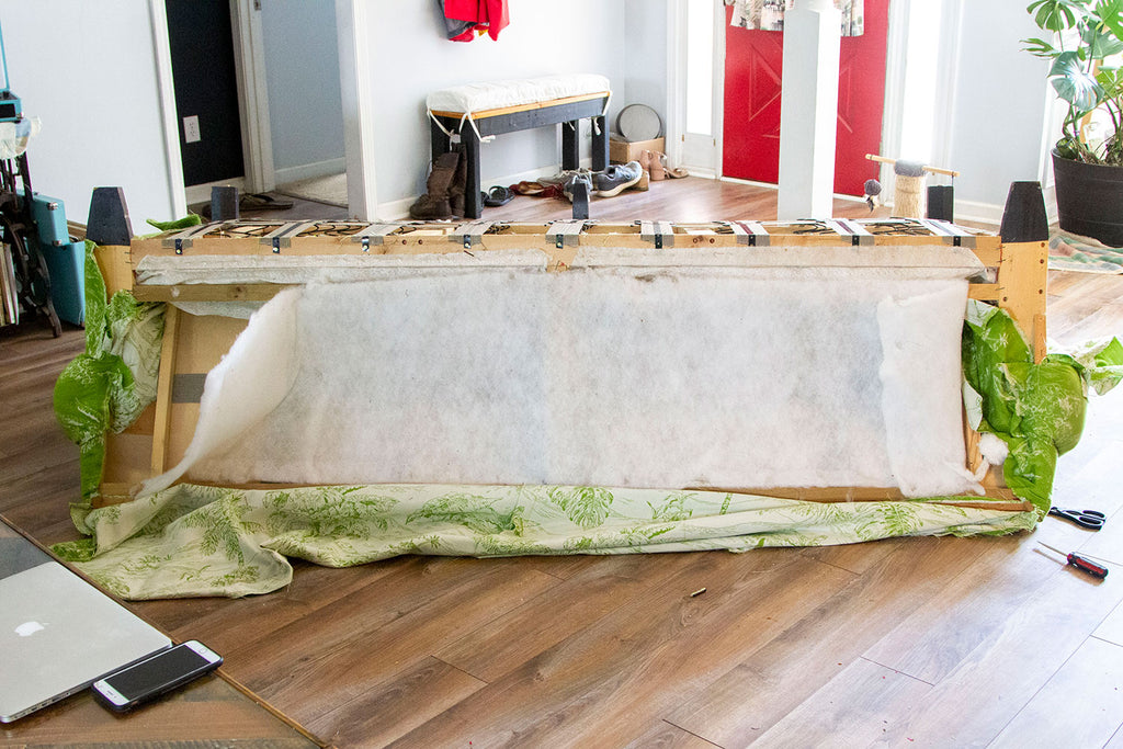 Couch turned upside down with the back panel removed exposing a white thin layer of batting