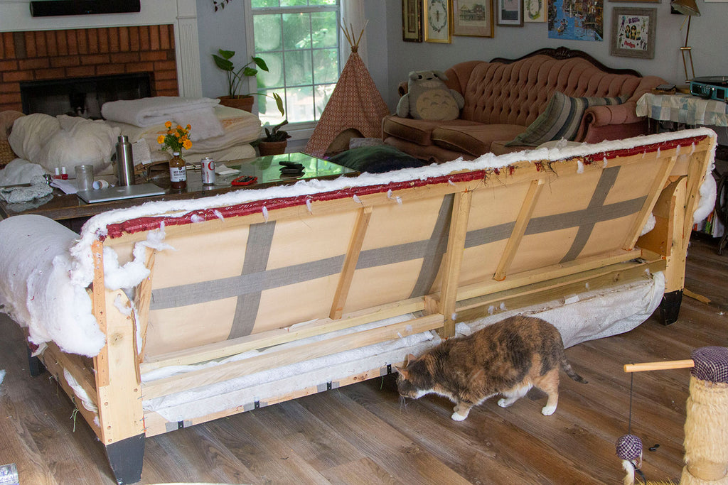 Fully stripped down couch showing the exposed back with all the wood supports and a bit of batting on the arms