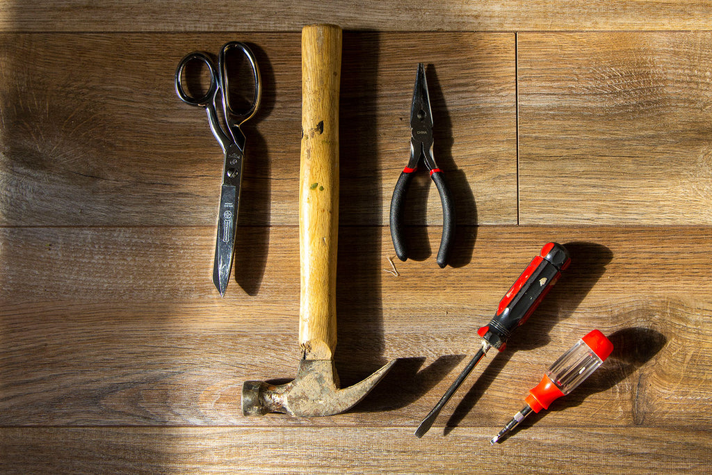 A flat lay of a pair of screw drivers, pliers , hammer, and scissors all laid out on a dark wooden floor.