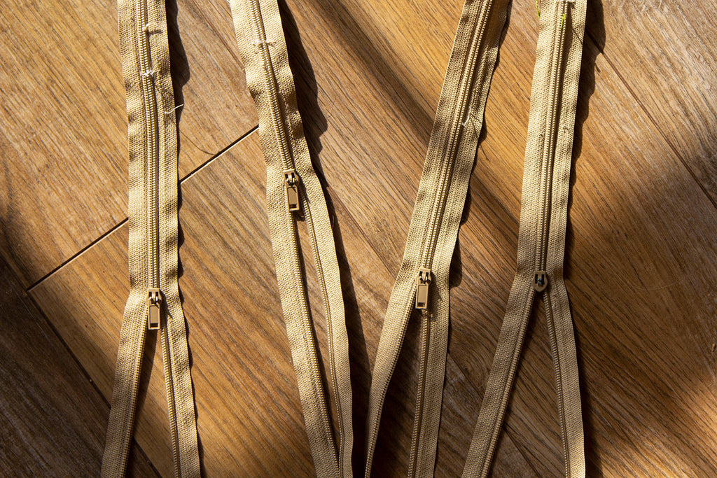 A set of four taupe colored zippers lying on a dark wooden floor with the shadows of a window streaming over them