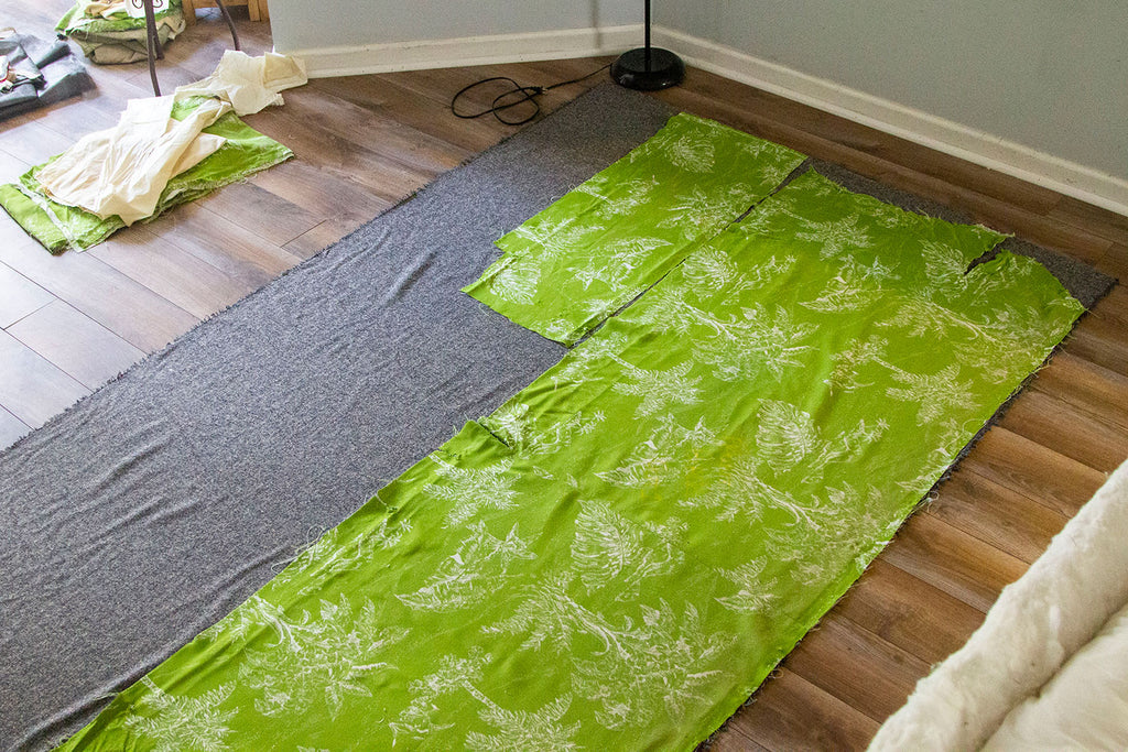 First two pattern pieces of lime green fabric laid out on top of a single layer of the grey wool fabric