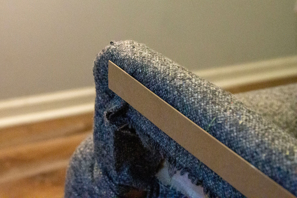 A strip of compressed cardboard lays flush against the top corner of the couch's back, prior to being stapled.