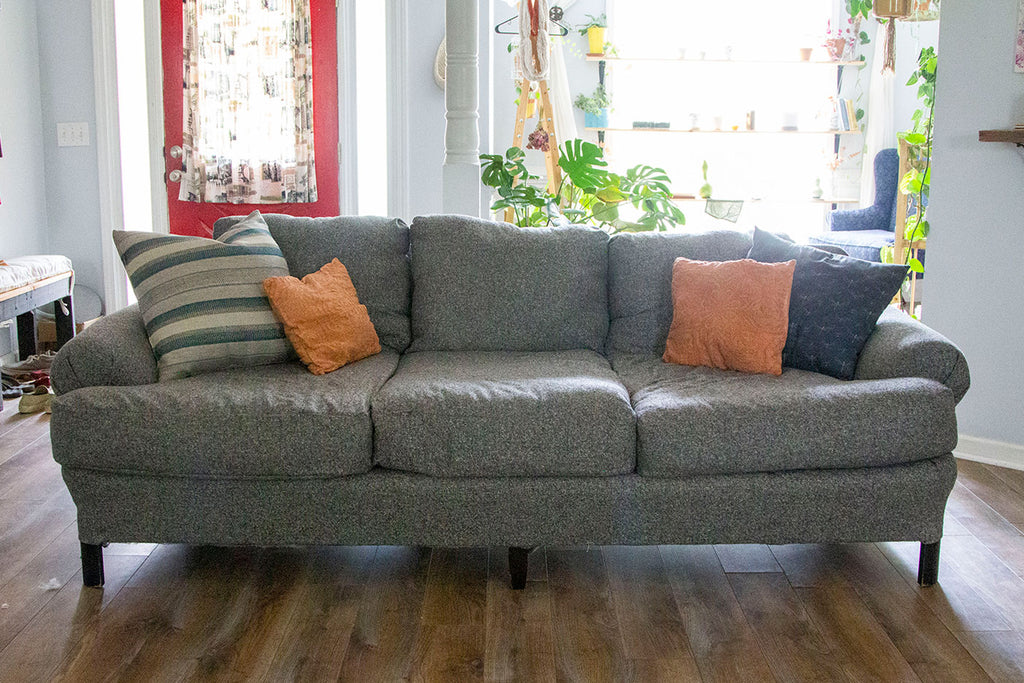 A straight on angle view of the new grey couch completed with three lower cushions, three upper cushions, two large blue pillows on either side (one striped, one printed), and two orange cushions on either side. Bright light stream in from behind the couch