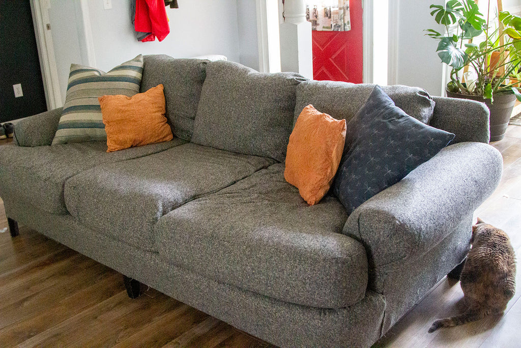 A side angle iew of the new grey couch completed with three lower cushions, three upper cushions, two large blue pillows on either side (one striped, one printed), and two orange cushions on either side.