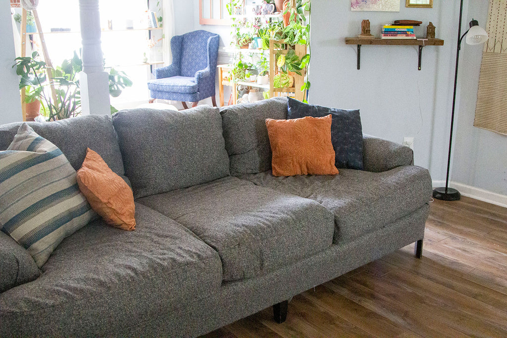 A side angle view (opposite of the first) of the new grey couch completed with three lower cushions, three upper cushions, two large blue pillows on either side (one striped, one printed), and two orange cushions on either side.