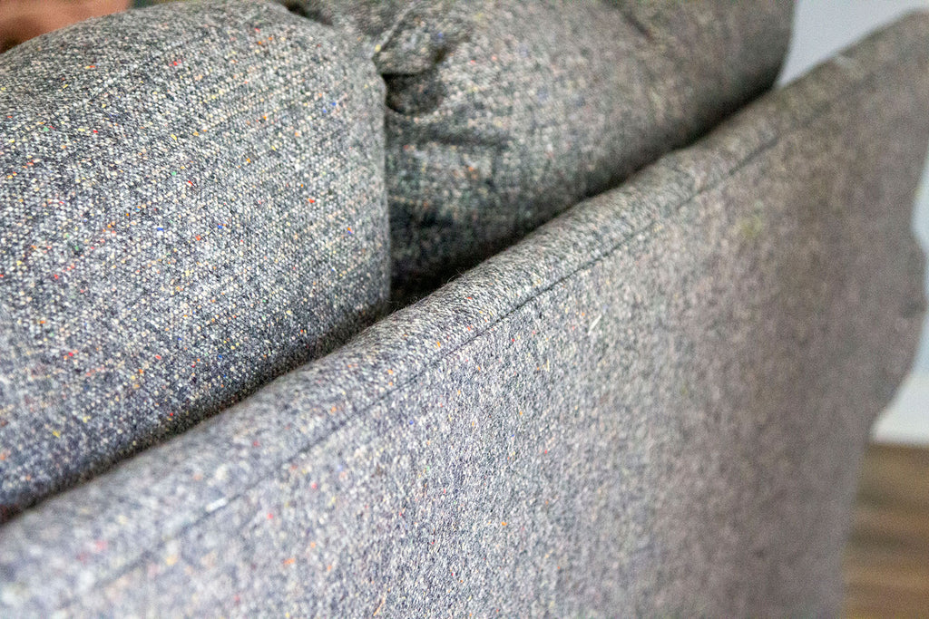 A close up of the upper part of the couch's back panel showcasing a crisp seam along the edge